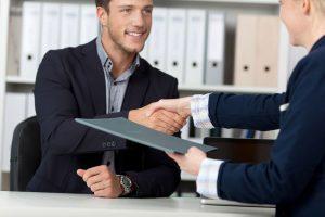 Homme et femme se serrant la main après conclusion d'un dossier