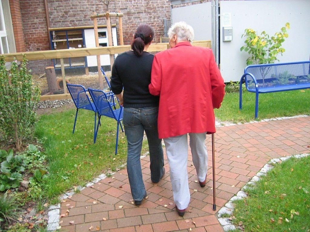 Personne âgée en promenade avec un soignant