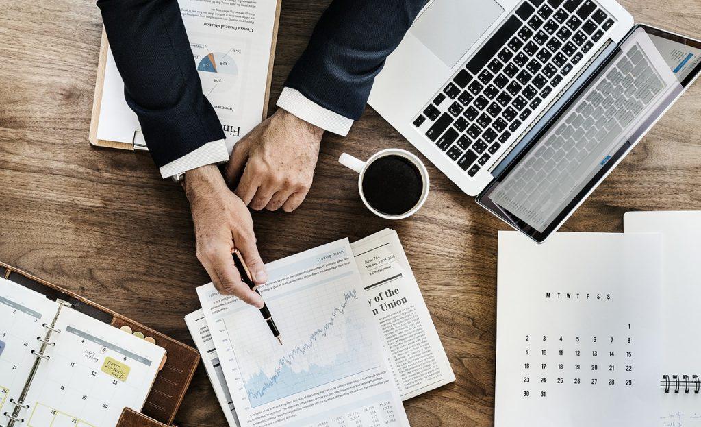 personne montrant un document posé sur une table à côté d'un ordinateur portable d'un carnet de document et d'une tasse de café